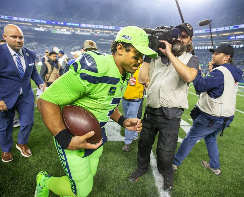 Seahawks quarterback Russell Wilson runs off the field after Seattle's win over the Rams. (Mike Siegel / The Seattle Times)