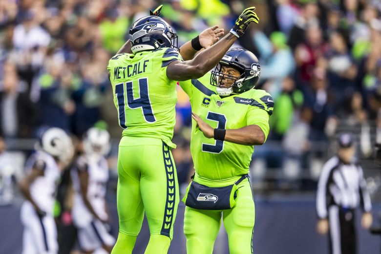 Seahawks wide receiver DK Metcalf and quarterback Russell Wilson celebrate their 40-yard touchdown in the second quarter of Seattle's win over the Rams at CenturyLink Field.  (Andy Bao / The Seattle Times)