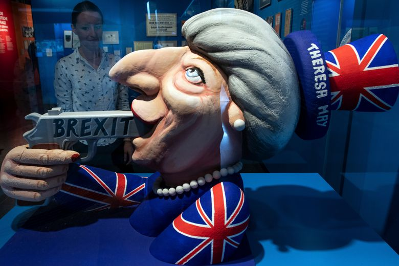 FILE – In this Tuesday July 9, 2019 file photo a woman looks to a model of a carnival float from Duesseldorf depicting British Prime Minister Theresa May and the Brexit at the exhibition 'Very British' about the Germany- Britain relationship at the German House Of History museum in Bonn, Germany. (Federico Gambarini/dpa via AP, file)