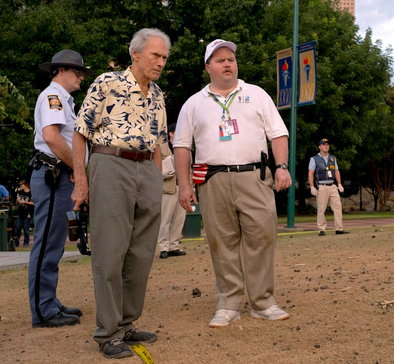 """This image released by Warner Bros. Pictures shows writer-director Clint Eastwood, left, and actor Paul Walter Hauser during the filming of """"Richard Jewell."""" The film will have its world premiere at the AFI Fest in Los Angeles in November. Hauser portrays the title character who went from hero to suspect after the 1996 Atlanta Olympic bombing that killed one woman. (Clair Folger/Warner Bros. Pictures via AP)"""
