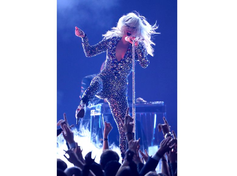 FILE – This Feb. 10, 2019 file photo shows Lady Gaga performing at the Grammy Awards in Los Angeles. Lady Gaga is recovering after falling off stage while dancing with a fan at a concert. During her Las Vegas show Thursday night, the pop star invited a fan onstage who picked her up and lost balance, and both plunged to the floor as a result. (Photo by Matt Sayles/Invision/AP, File)