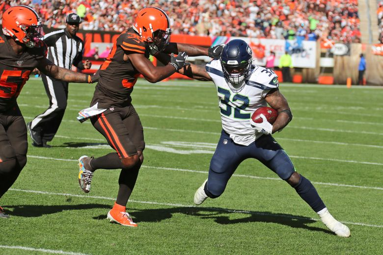 Seattle Seahawks running back Chris Carson (32) avoids a tackle by Cleveland Browns defensive back T.J. Carrie (38) during the second half of an NFL football game, Sunday, Oct. 13, 2019, in Cleveland. (AP Photo/Ron Schwane)