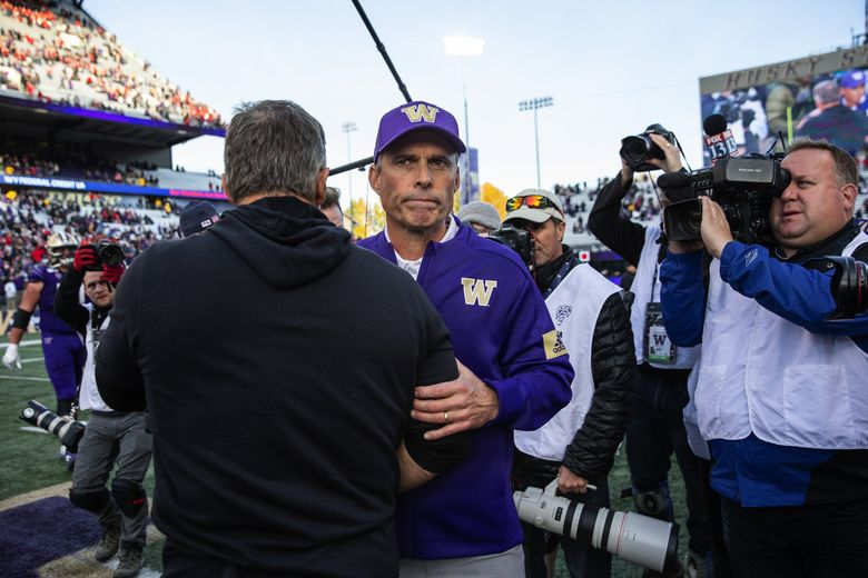 A disappointed Chris Petersen shakes hands with Utah coach Kyle Whittingham after the Huskies lost Saturday 33-28. (Dean Rutz / The Seattle Times)