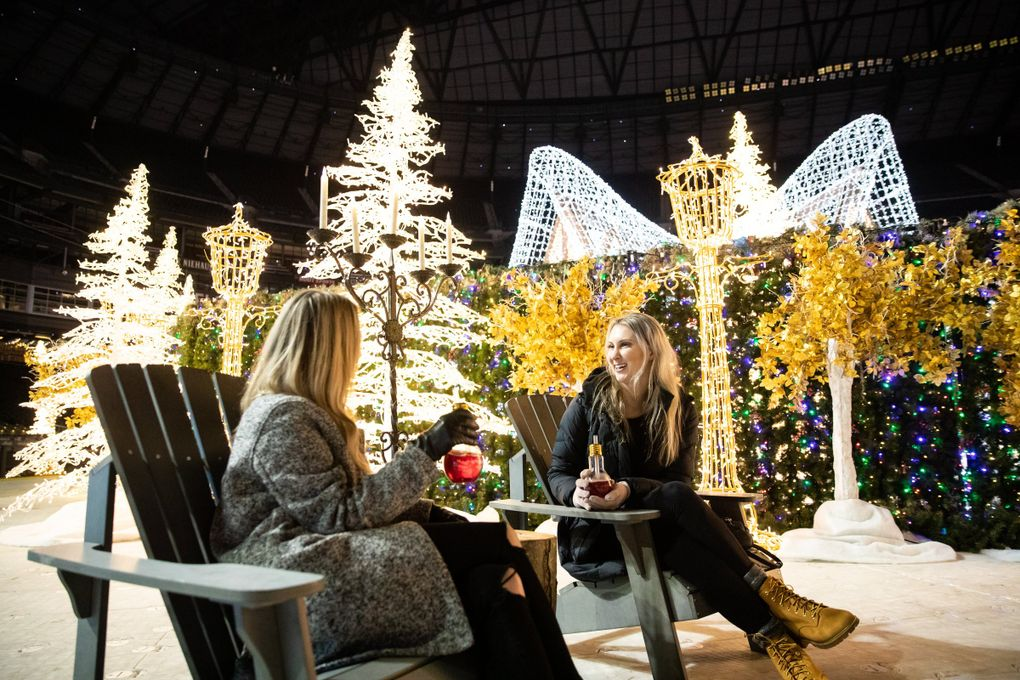 """Robyn Stewart left, and Julie Jones sip their Enchant vodka-cranberry cocktails at Enchant Christmas. """"It was $15 but it lights up"""" said Stewart.  (Andy Bao / The Seattle Times)"""
