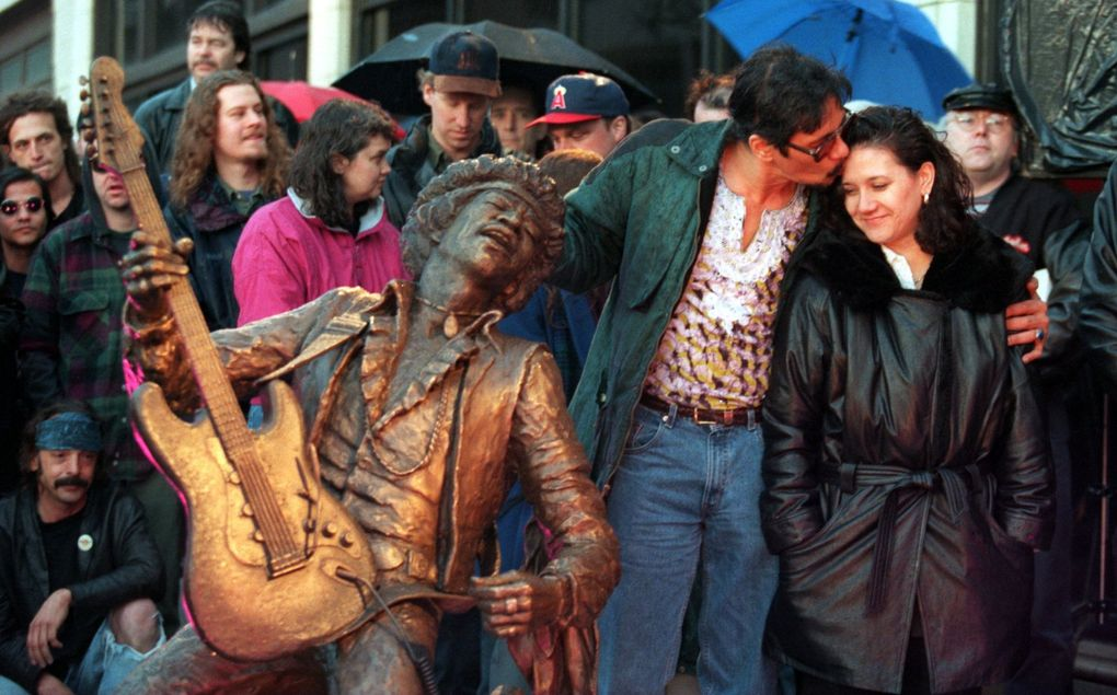 Leon Hendrix kisses his sister, Janie Hendrix, at the 1997 unveiling of a statue of their brother Jimi Hendrix on Capitol Hill. The  statue is on permanent display at the intersection of Broadway Avenue and Pine Street. (Benjamin Benschneider / The Seattle Times)