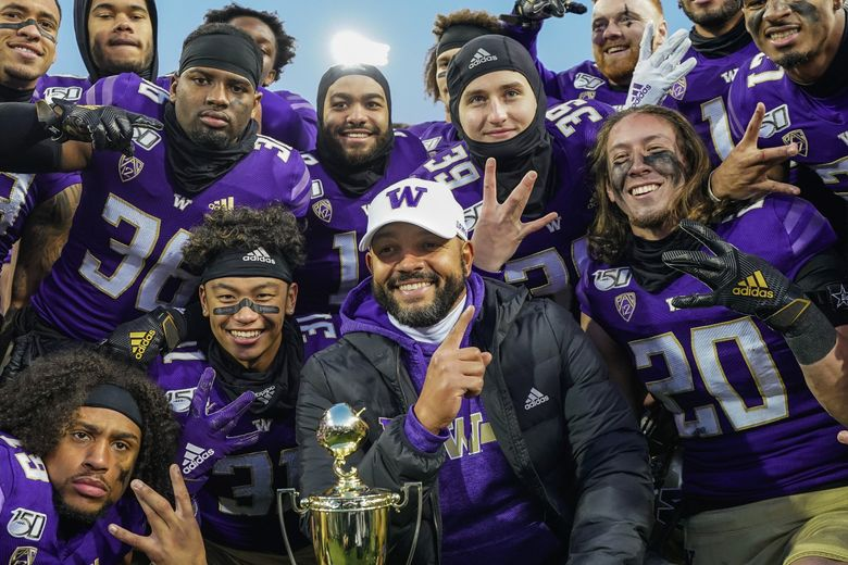 Jimmy Lake and his defensive unit pose with the Apple Cup trophy after Washington defeated WSU 31-13 Friday.  (Dean Rutz / The Seattle Times)