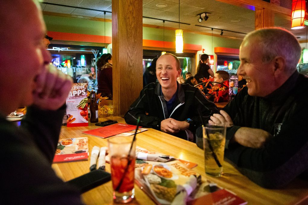 """Referee Tyler Trimble, center, grabs drinks at Applebee's with fellow referees after a Friday night football game between Adna High School and Onalaska High School in Adna on Oct. 25. """"We're real people. We enjoy the sport and love what we do"""" Trimble said.  (Andy Bao / The Seattle Times)"""