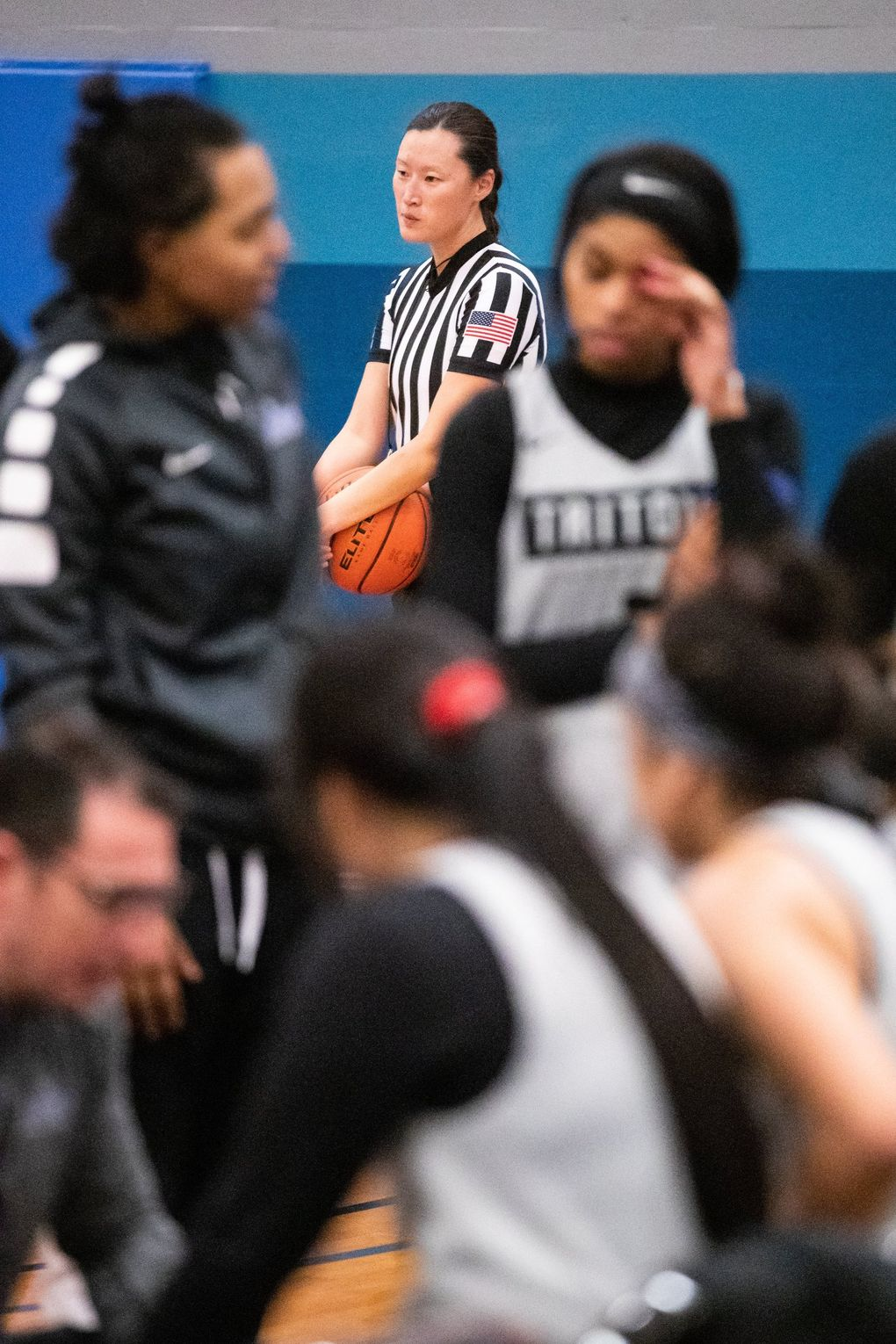 """Referee Jillian Quinn waits during a timeout in a women's basketball scrimmage. The pool of referees is shrinking while organizations struggle to bring aboard new officials. """"There's just more open games than officials,"""" Quinn said. """"If you were a kid and you could make $20 an hour reffing a basketball game but were getting verbally abused, why would you want to do that?""""  (Andy Bao / The Seattle Times)"""