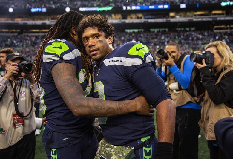Shaquill Griffin hugs a weary Russell Wilson after the Seahawks defeated Tampa Bay at CenturyLink Field last Sunday. (Dean Rutz / The Seattle Times)