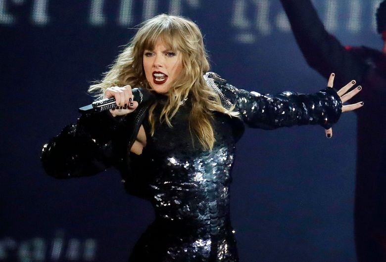 """FILE – This May 8, 2018 file photo shows Taylor Swift performing during her """"Reputation Stadium Tour"""" opener in Glendale, Ariz. Swift says she may not be performing at the American Music Awards because the men who own her old recordings won't allow her to play her songs.  Swift said on Instagram Thursday that she planned to play a medley of her hits when she's named Artist of the Decade at the American Music Awards on Nov. 24. But Swift says the men who own the music, Scooter Braun and Scott Borchetta, are calling the performance an illegal re-recording.  (Photo by Rick Scuteri/Invision/AP, File)"""