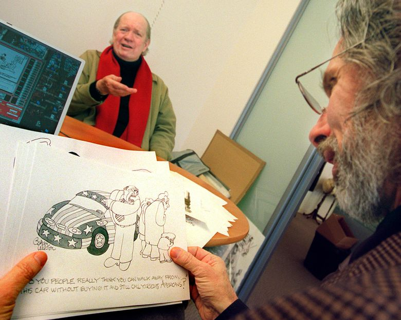 FILE- In this Nov. 27, 2001 file photo, cartoonist Gahan Wilson gestures as New Yorker cartoon editor Robert Mankoff looks over Wilson's offerings at the magazine's offices in New York. Wilson, a cartoonist whose work appeared in National Lampoon and other publications and was known for depicting humor in the macabre, has died at 89. Stepson Paul Winters says Wilson died Nov. 21, 2019, in Scottsdale, Arizona, from complications of dementia. Wilson delighted readers with his haunting scenes and dark humor. (AP Photo/Kathy Willens, File)