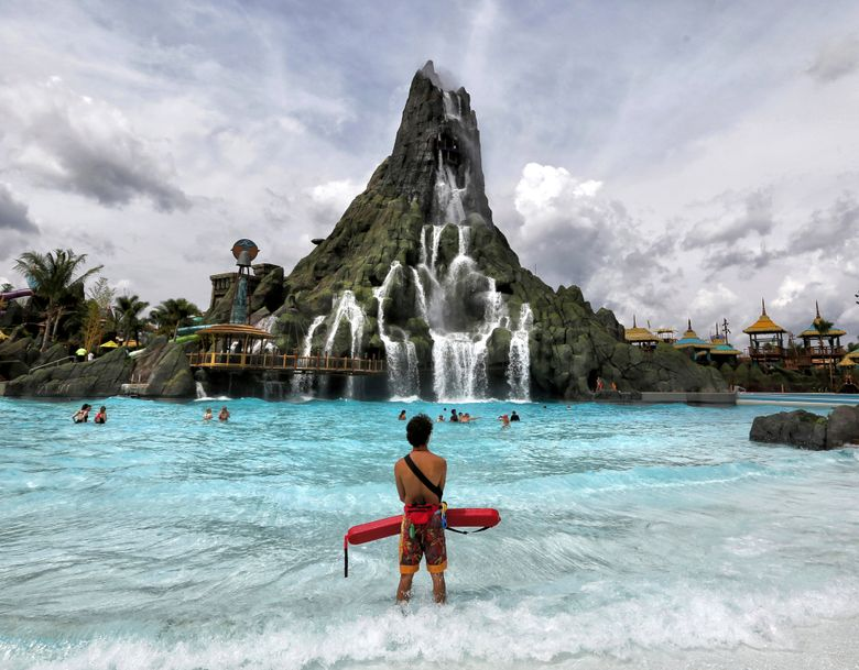 FILE- In this May 25, 2019, file photo, a lifeguard stands watch near the Krakatau volcano, the centerpiece water attraction at Universal Orlando's Volcano Bay, during a media preview in Orlando, Fla. Federal investigators say the resort won't be cited for electrical problems that led to lifeguards getting shocked at its water park, saying the resort was unaware something was wrong. The report released this week said that five lifeguards reported receiving electric shocks last June at the Volcano Bay water park. (Joe Burbank/Orlando Sentinel via AP, FIle)