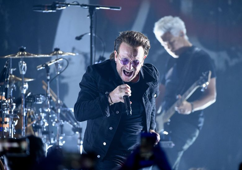 FILE – In this June 11, 2018 file photo,  Bono of U2 performs during a concert at the Apollo Theater in New York.  U2 raked in over $1 billion in sales to be named the artist of the decade by Pollstar. The touring trade publication tracks data on tours globally. It says U2 grossed $1.03 billion in ticket sales from November 2009 to November 2019. (Photo by Evan Agostini/Invision/AP, File)