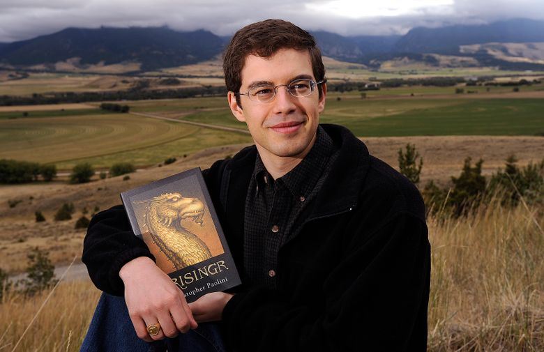 """FILE – This Sept. 13, 2008 file photo shows Christopher Paolini posing with his book """"Brisingr"""" in Paradise Valley, Mont. The author of the multimillion-selling """"Inheritance Cycle"""" has a 7-figure deal for a science fiction novel, his first adult book, Tor announced Tuesday. """"To Sleep in a Sea of Stars,"""" featuring """"epic space battles for the fate of humanity,"""" comes out next September. (AP Photo/David Grubbs, File)"""