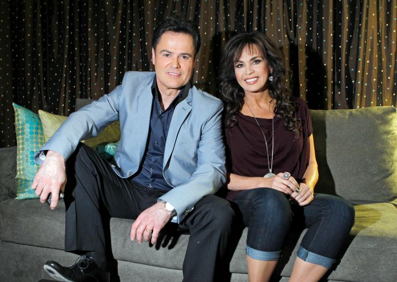 """FILE – In this April 28, 2011 file photo, siblings Donny Osmond, left, and Marie Osmond pose backstage at their show at the Flamingo hotel and casino in Las Vegas. Marie Osmond says she's ready for the final week of an 11-year run with her brother, Donny, at the Flamingo Las Vegas, after telling the audience on her television talk show that she chipped her knee late last week. Osmond talked about her injury during an appearance Monday, Nov. 11, 2019 on """"The Talk."""" She and her brother, who is 62, each have had hits with songs such as 'Puppy Love' and 'Paper Roses.' (AP Photo/Isaac Brekken, File)"""