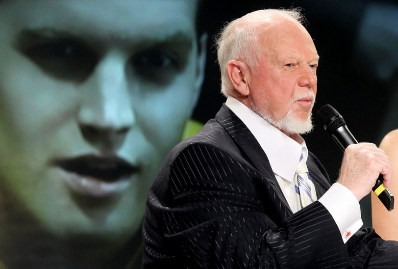 """FILE _ In this March 24, 2010, file photo, hockey personality Don Cherry, right, speaks during a news conference as actor Jared Keeso is displayed on a video screen while playing Cherry in the bio film """"Keep Your Head Up Kid: The Don Cherry Story"""" in Toronto. Sportsnet cut ties with Cherry on Monday, Nov. 11, 2019, after the veteran hockey commentator called new immigrants """"you people"""" on his """"Coach's Corner"""" segment while claiming they do not wear poppies to honor Canadian veterans. (AP Photo/The Canadian Press, Darren Calabrese, File)"""
