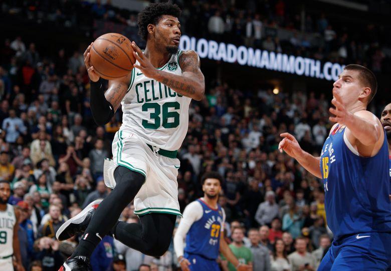 Boston Celtics guard Marcus Smart pulls in a rebound as Denver Nuggets center Nikola Jokic defends during the second half of an NBA basketball game Friday, Nov. 22, 2019, in Denver. The Nuggets won 96-92. (AP Photo/David Zalubowski)