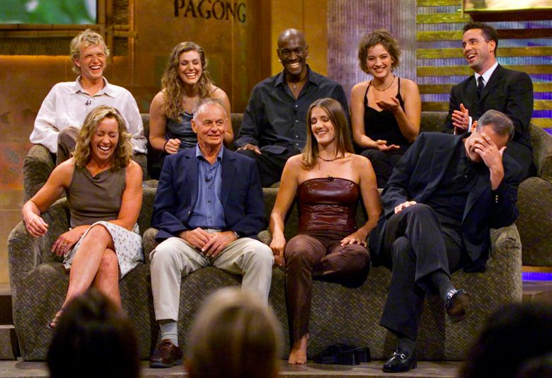 """FILE – In this Aug. 23, 2000, file photo, a group of """"Survivor"""" contestants, break into laughter during a live town hall meeting at CBS Studios in Hollywood in Los Angeles. Survivors are, from left, bottom row, Susan Hawk, Rudy Boesch, Kelly Wiglesworth and Richard Hatch, covering his face, top row, Greg Buis, Jenna Lewis, Gervase Peterson, Colleen Haskell and Sean Kenniff. Boesch, a retired tough-as-nails Navy SEAL and fan favorite on the inaugural season of """"Survivor,"""" died Friday, Nov. 1, 2019, after a long battle with Alzheimer's disease. He was 91. (AP Photo/Kevork Djansezian, File)"""