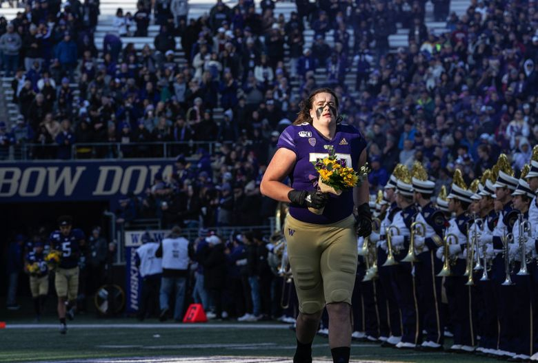 Trey Adams comes out with flowers for his mother on Senior Day before the Apple Cup game at Husky Stadium in Seattle, WA Friday, November 29, 2019. (Dean Rutz / The Seattle Times)
