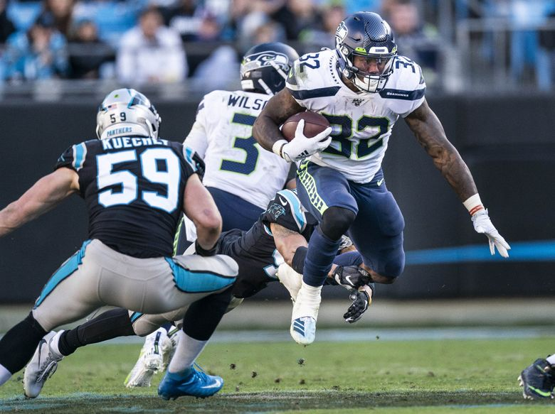 Chris Carson hops through a hole and gains 4 to the 46 in the 3rd quarter.  The Seattle Seahawks played the Carolina Panthers Sunday, December 15 at Bank of America Stadium in Charlotte, NC. (Dean Rutz / The Seattle Times)