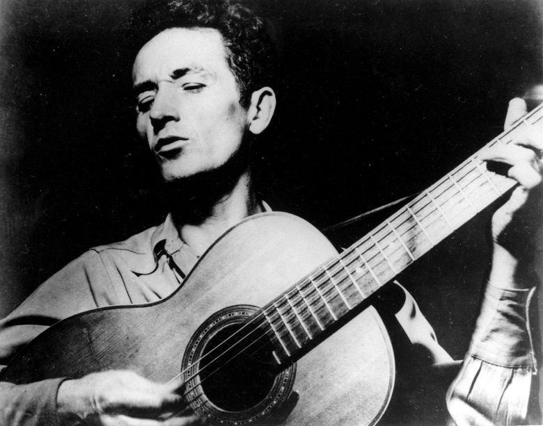 """FILE- In this undated photo Oklahoma folk singer Woody Guthrie plays his guitar. The Woody Guthrie Center in Tulsa announced Tuesday, Dec. 10, 2019, that there will be a 80th anniversary concert of Guthrie's classic song, """"This Land Is Your Land."""" at The Town Hall in New York. The venue is near where Guthrie is believed to have written the song on Feb. 23, 1940. (AP Photo, file)"""