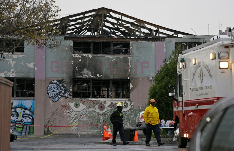 FILE – This Dec. 7, 2016 file photo shows Oakland fire officials walk past the remains of the Ghost Ship warehouse damaged from a deadly fire in Oakland, Calif. Anger over plans for a television series about a deadly warehouse fire in the San Francisco Bay Area has led husband-and-wife authors Michael Chabon and Ayelet Waldman to scuttle the project for now. The Berkeley, California-based couple said Saturday, Dec. 14, 2019, that since word got out that they were in the early stages of developing a New York Times Magazine article about the 2016 fire at the Ghost Ship warehouse for TV, many friends and families of the victims have urged them to reconsider the project because it was too soon for them to relive the tragedy. (AP Photo/Eric Risberg, File)