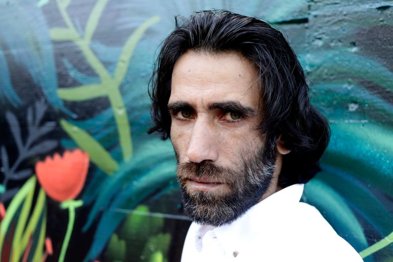 FILE – In this Nov. 19, 2019, file photo, Behrouz Boochani, the Kurdish film-maker, writer and refugee who has documented life inside the Australian offshore immigration camp on Manus Island, poses for a portrait in Christchurch, New Zealand.  The refugee who wrote an award-winning book while being held in detention has overstayed his visa in New Zealand, according to at least one official and the man's lawyer, in a move that could fuel diplomatic tensions with Australia. (AP Photo/Mark Baker, File)