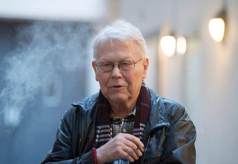 """File—Picture taken March 13, 2019 shows irector Harry Kupfer smokes during the break of the photo rehearsal of Handel's opera """"Poros"""" in a courtyard of the Komische Oper, Berlin, Germany. Kupfer died on Monday. (Soeren Stache/dpa via AP)"""