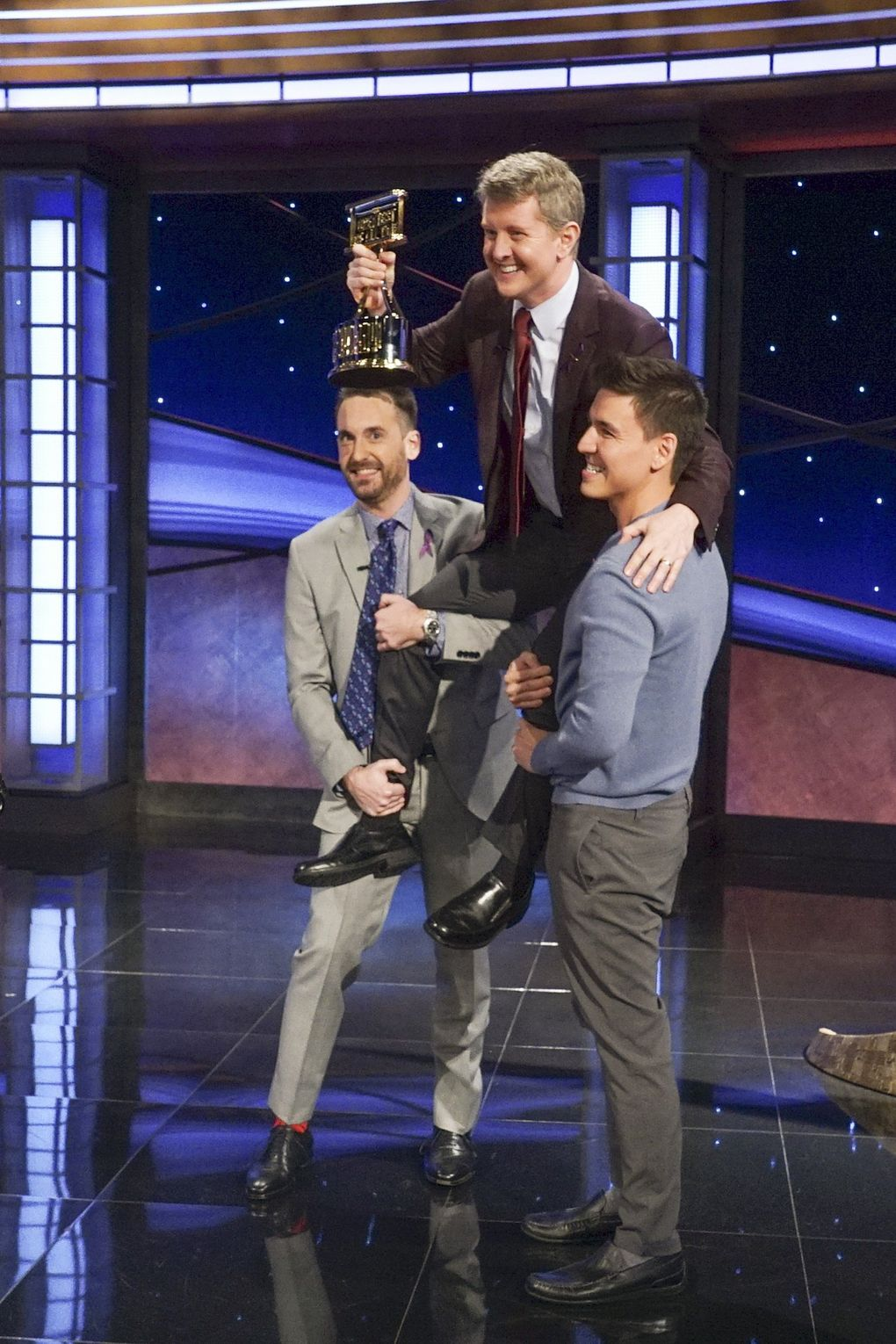 """Seattle's Ken Jennings is hoisted by his """"Jeopardy! The Greatest of All Time"""" competitors James Holzhauer, right, and Brad Rutter. Jennings has earned more than $3.5 million from his appearances on the show. (Eric McCandless / ABC)"""