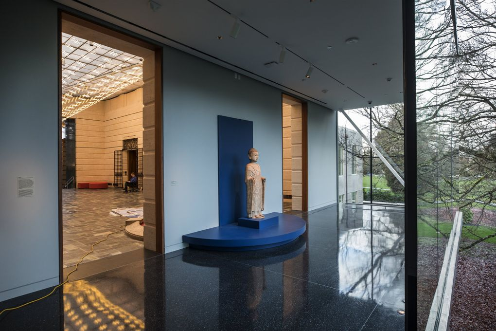 """The Chinese marble sculpture """"Standing Buddha,"""" dating to the sixth century, is positioned at the divide between Seattle Asian Art Museum's old 1933 building and its new, glassy addition. (Steve Ringman / The Seattle Times)"""
