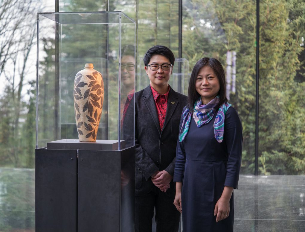 Curators Ping Foong and Xiaojin Wu stand in the new, glassed-in terrace at the renovated Seattle Asian Art Museum.    (Steve Ringman / The Seattle Times)