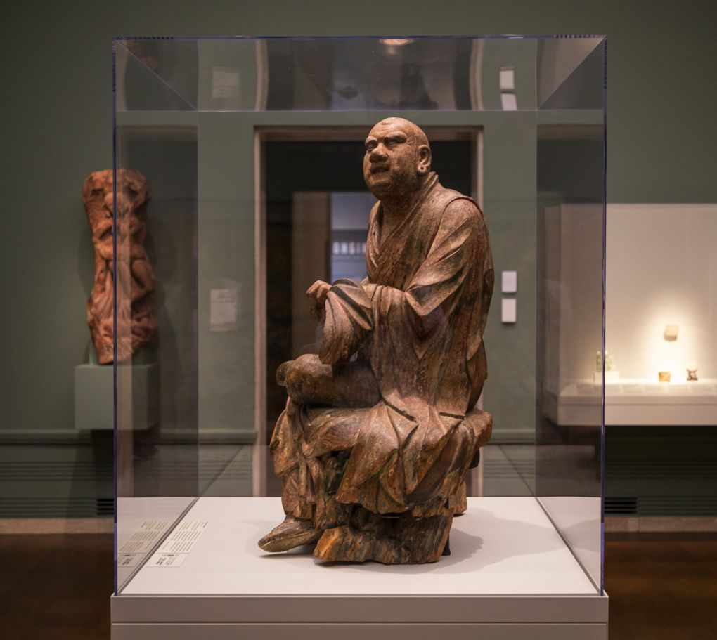 """The Dragon Tamer Luohan, which had long been misidentified as a monk at the moment of enlightenment, stands in the """"Bringing Blessings"""" gallery at Seattle Asian Art Museum. (Steve Ringman / The Seattle Times)"""