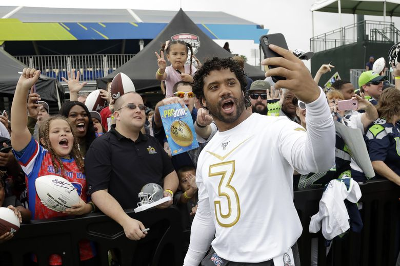 NFC quarterback Russell Wilson, of the Seattle Seahawks, live videos fans after a practice for the NFL Pro Bowl football game Thursday, Jan. 23, 2020, in Kissimmee, Fla. (AP Photo/Chris O'Meara) FLCO102 FLCO102 (Chris O'Meara / The Associated Press)