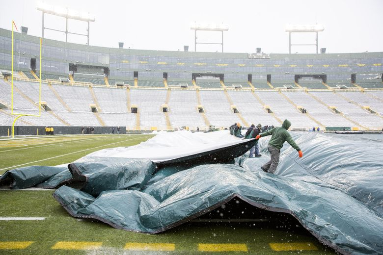 The tarp is taken off the field after snow is cleared before the Seattle Seahawks take on the Green Bay Packers at Lambeau Field in Green Bay, Wisconsin Sunday December 11, 2016.  (Bettina Hansen / The Seattle Times)