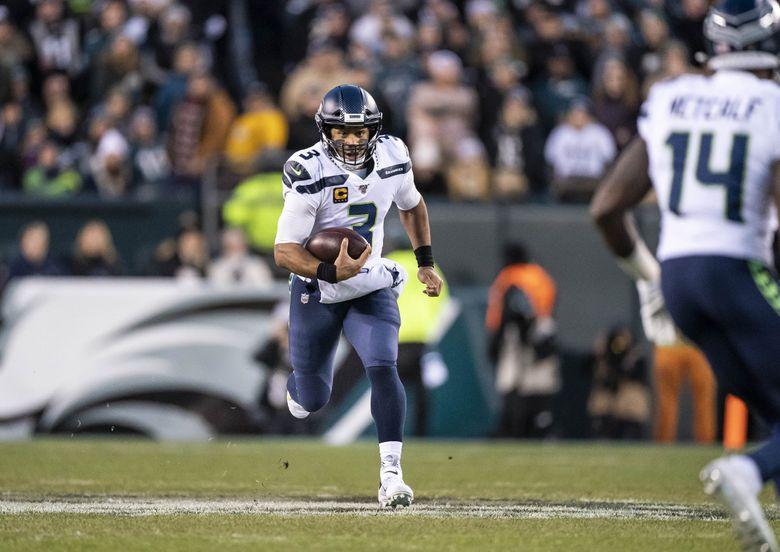 Seahawks quarterback Russell Wilson breaks through for a first-down Sunday against the Eagles last season. (Dean Rutz / The Seattle Times)
