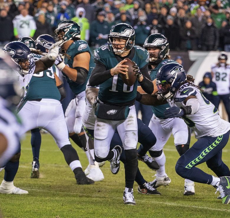Seattle Seahawks defensive tackle Jarran Reed, left, and defensive end Jadeveon Clowney (90) take down Philadelphia Eagles quarterback Josh McCown (18) late in the fourth quarter, ending their last drive on Sunday, Jan. 5, 2020 at Lincoln Financial Field in Philadelphia, Pa.
