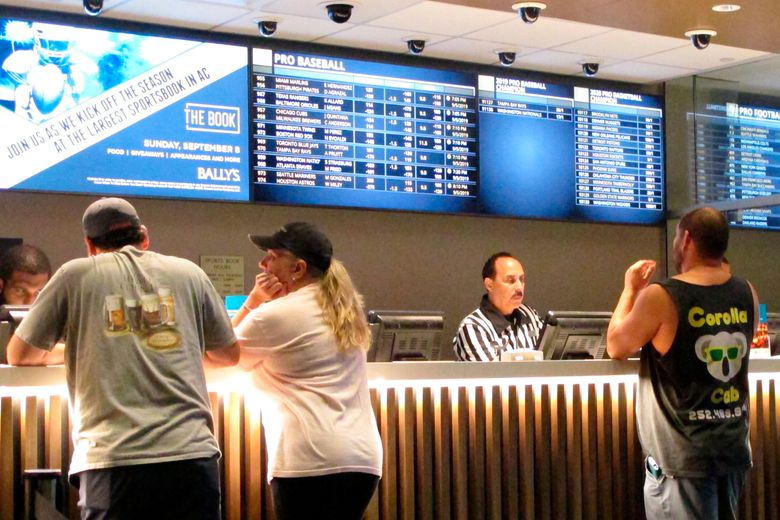 In this Sept. 5, 2019 photo, gamblers place sports bets at Bally's casino in Atlantic City, N.J. (AP Photo/Wayne Parry)