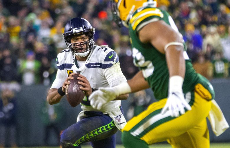 Seattle Seahawks quarterback Russell Wilson (3) looks for options down field as the Green Bay Packers play the Seattle Seahawks at Lambeau Field in Green Bay Wisconsin on January 12, 2020.   212648 (Mike Siegel / The Seattle Times)