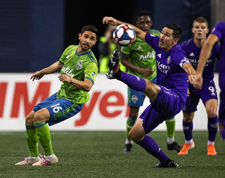Orlando's Sacha Kljestan, right, tries to keep a drive alive by denying Seattle's Alex Roldan in stoppage time in May 2019. (Dean Rutz / The Seattle Times)