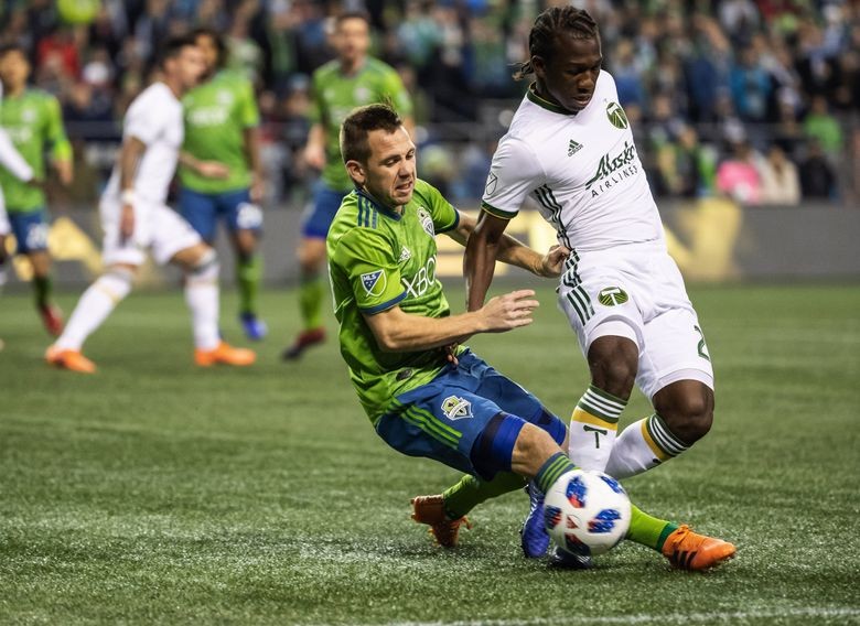 Harry Shipp slide tackles Portland's Diego Chara in a 2018 game. (Dean Rutz / The Seattle Times)