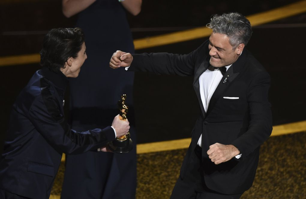 """Timothee Chalamet, left, presents the award for best adapted screenplay to Taika Waititi for """"Jojo Rabbit"""" at the Oscars on Sunday, Feb. 9, 2020, at the Dolby Theatre in Los Angeles. (AP Photo/Chris Pizzello) CADC227 CADC227 (Chris Pizzello / Chris Pizzello/Invision/AP)"""