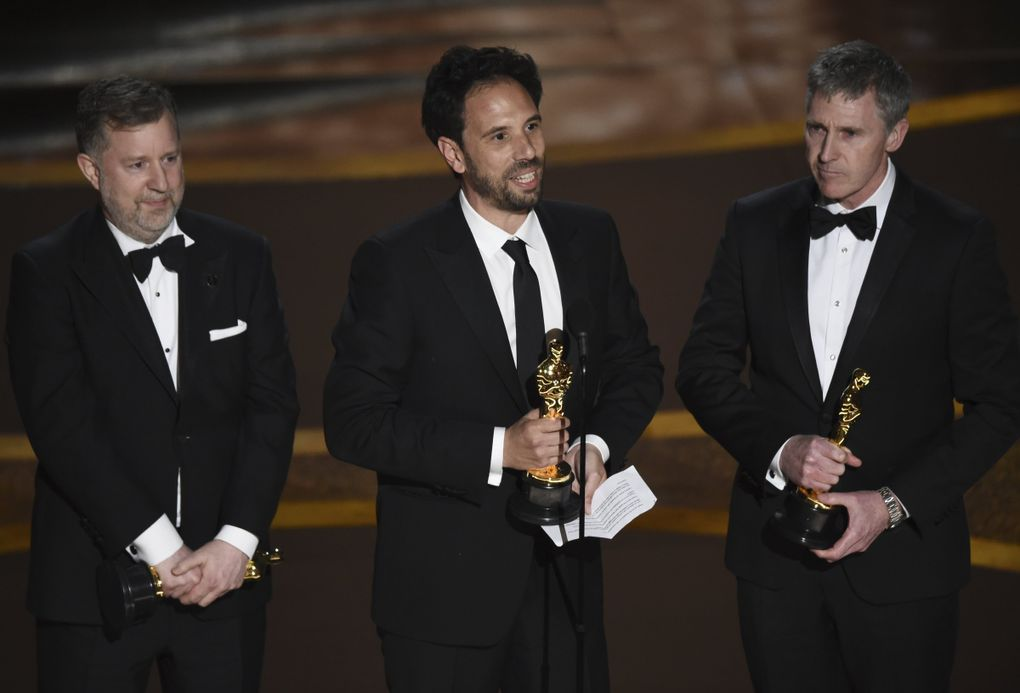 """Greg Butler, from left, Guillaume Rocheron and Dominic Tuohy accept the award for best visual effects for """"1917"""" at the Oscars on Sunday, Feb. 9, 2020, at the Dolby Theatre in Los Angeles. (AP Photo/Chris Pizzello) CADC348 CADC348 (Chris Pizzello / Chris Pizzello/Invision/AP)"""