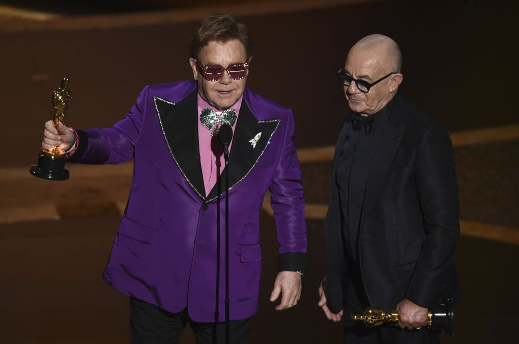 """Elton John, left, and Bernie Taupin accept the award for best original song for """"(I'm Gonna) Love Me Again"""" from """"Rocketman"""" at the Oscars on Sunday, Feb. 9, 2020, at the Dolby Theatre in Los Angeles. (AP Photo/Chris Pizzello) CADC375 CADC375 (Chris Pizzello / Chris Pizzello/Invision/AP)"""