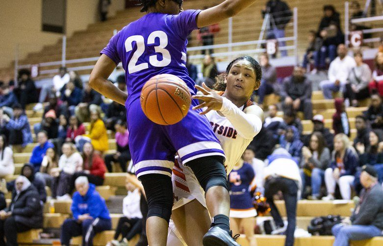 Eastside Catholic freshman Malia Samuels goes down the court for a break away and passes the ball around Garfield senior Kareyna Taylor in the Metro League title game. (Amanda Snyder/The Seattle Times)