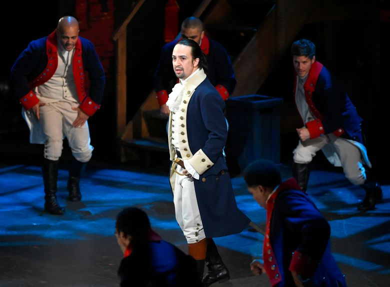 """FILE – In this June 12, 2016 file photo, Lin-Manuel Miranda and the cast of """"Hamilton"""" perform at the Tony Awards in New York.  Next year, you'll be able to see the original Broadway cast of """"Hamilton"""" perform the musical smash from the comfort of a movie theater. The Walt Disney Company said Monday, Feb. 3, 2020, it will distribute a live capture of Lin-Manuel Miranda's show in the United States and Canada on Oct. 15, 2021. (Photo by Evan Agostini/Invision/AP, File)"""