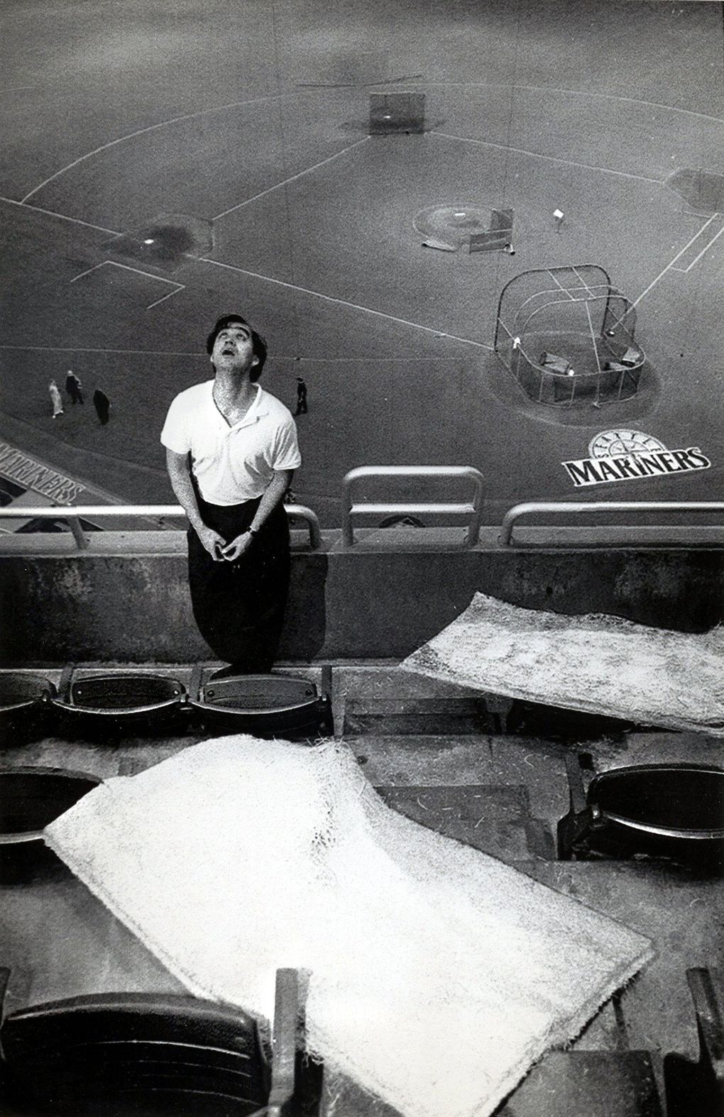 Tom Long, a Kingdome employee, examines the roof above the 300 level, where ceiling tiles fell onto some seats.  July 20, 1994.(Rod Mar / The Seattle Times)