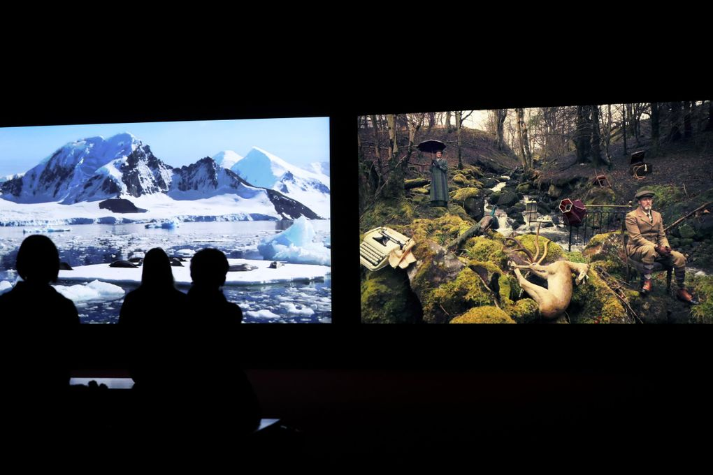 """Seattle Art Museum visitors watch """"Vertigo Sea"""" (2015), a film showing as part of the """"John Akomfrah: Future History,"""" exhibit. The film is split into three screens showing simultaneous images; only two screens are seen here. (Ken Lambert / The Seattle Times)"""