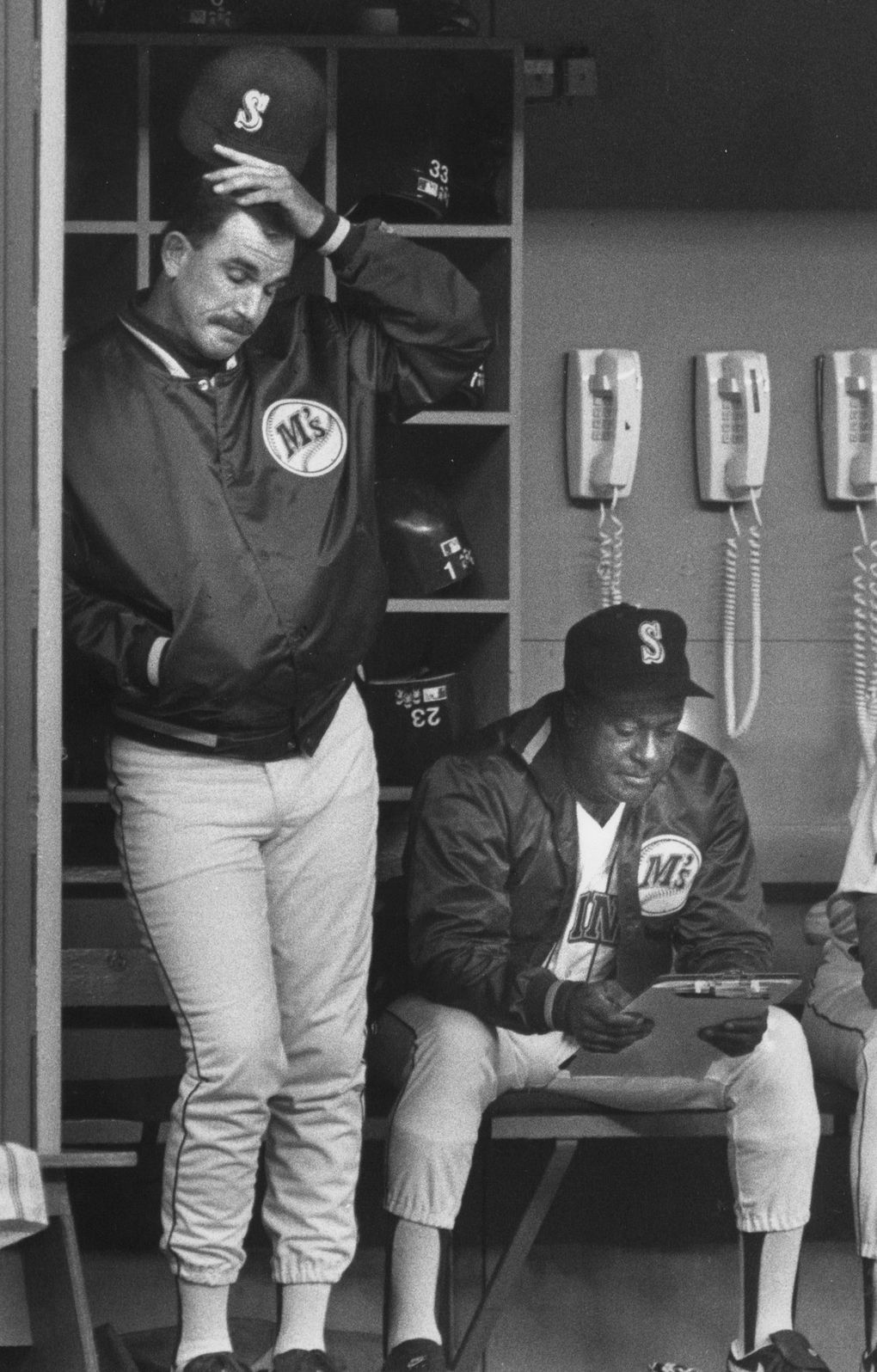 Mariners manager Bill Plummer watches a woeful team as hitting coach Gene Clines consults his clipboard. (Alan Berner / The Seattle Times, 1992 file)