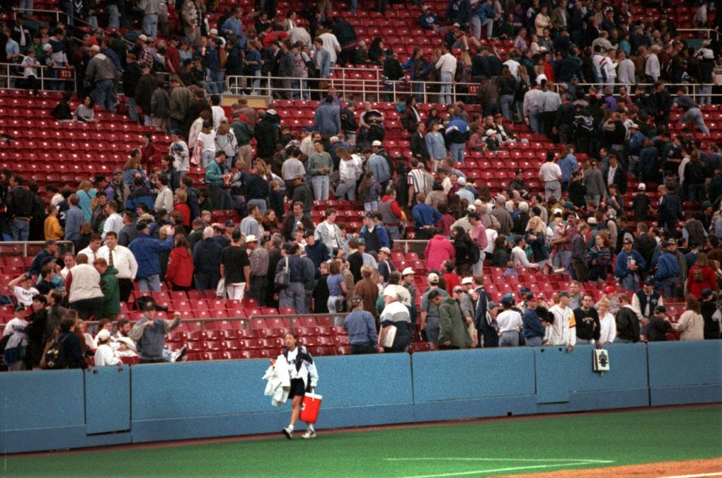 The ballgirl leaves the field and Mariner fans make a hasty but orderly exit from the Kingdome after the ballgame was suspended because of an earthquake. (Mark Harrison / The Seattle Times)
