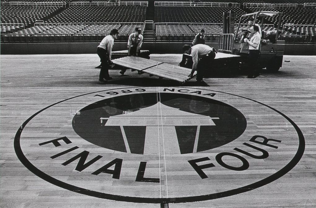 Workers install part of the hardwood floor for the Final Four at the Kingdome in 1989. (Jimi Lott / The Seattle Times)